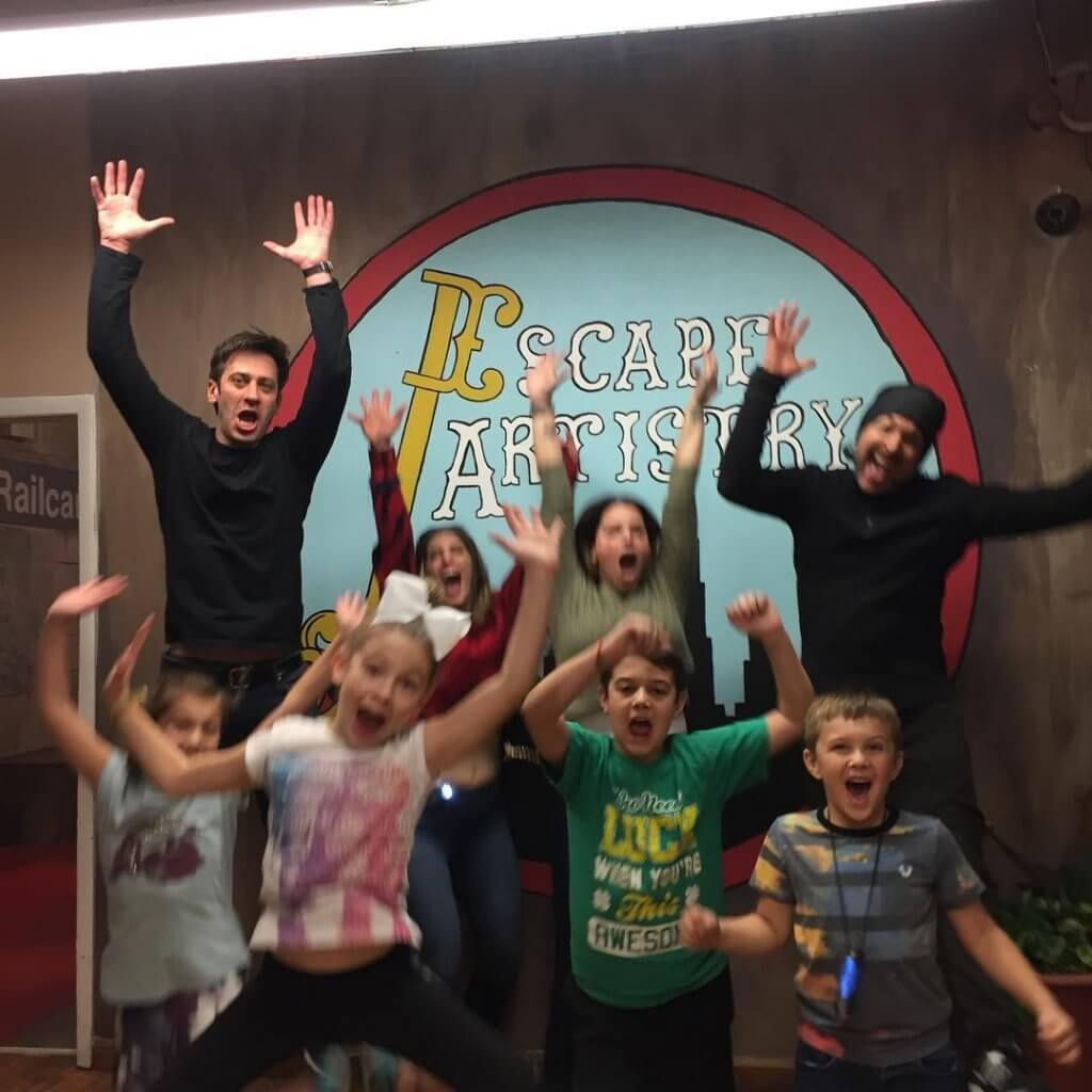 A group of men and children jumping in front of Escape Artisty's logo